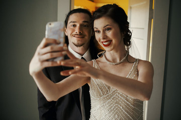 Bride takes a selfie of herself and groom standing in the room