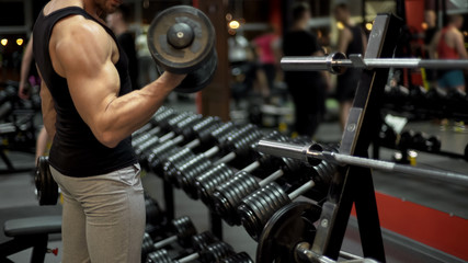 Muscleman lifting heavy dumbbells in gym, sport equipment, power bodybuilding
