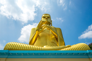 Huge golden Buddha statue on top of the Buddhist Museum of the Golden Temple Dambulla