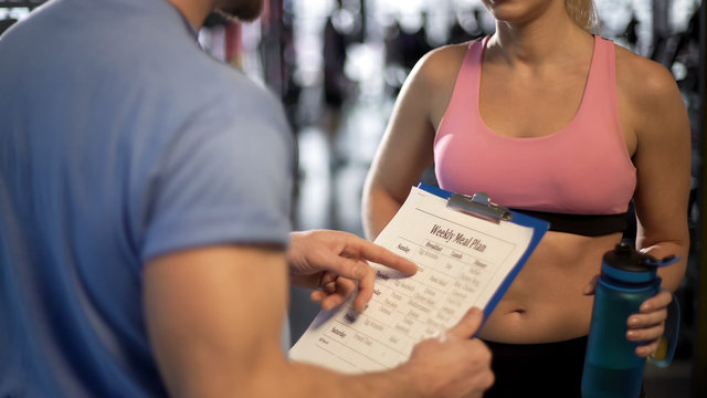 Personal trainer teaching client how to count calories, discussing meal plan