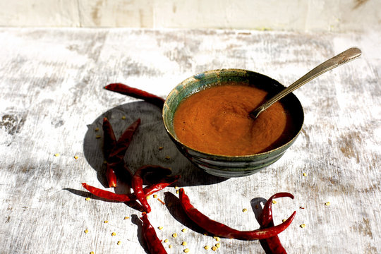 Bowl of Hot Sauce with Arbol Chili Peppers. Photographed on a rustic white background.
