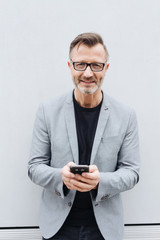 Smiling man in grey jacket using mobile phone