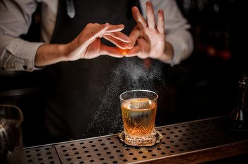 Aluminium Prints Cocktail Bartender adding juice from the orange zest to the fresh alcoholic drink