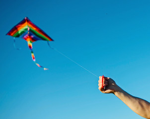 Mans hand with kite on blue sky.