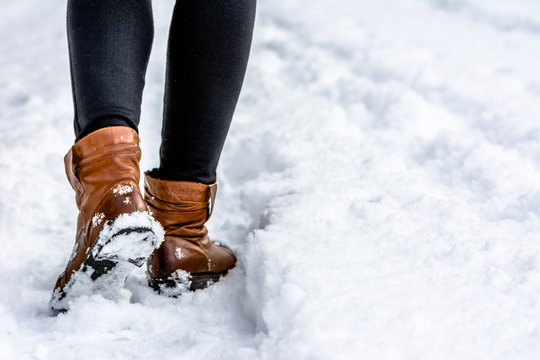 Brown boots in snow, woman put the step in snow, walking in winter