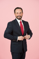 Portrait of styled man isolated in studio. Man in suit and red tied fasten jacket. Happy businessman fasten button on jacket of blue suit