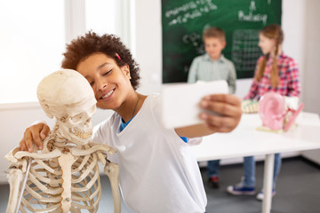 Joyful mood. Positive delighted boy standing near the skeleton while trying to take a selfie