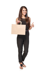 Full length woman holding carton brown shopping bag with empty copy space and gesturing thumb up