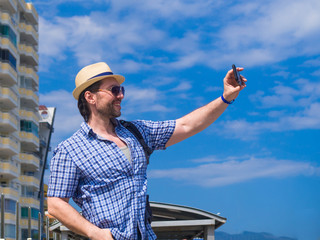 Delighted young man in trendy checkered shirt spending time outdoor, exploring the surroundings in morning. Smiling guy in hat and sunglasses having fun, during travel in Italy and making selfie.