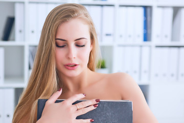 Fototapeta Beautiful young secretary hides her nakedness for a folder on an office background. Harassment concept. obraz