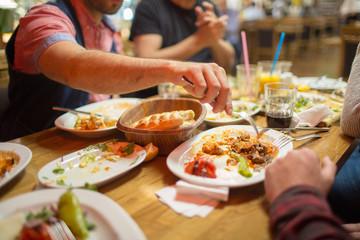 Group of Arab people in restaurant enjoying Middle Eastern food. Selective focus