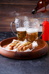 Image of two mugs of beer and hot dogs