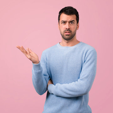 Handsome man unhappy and frustrated with something. Negative facial expression on pink background