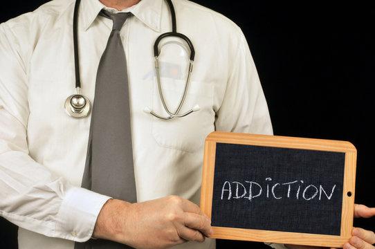 Médecin tenant une ardoise sur laquelle est écrit addiction