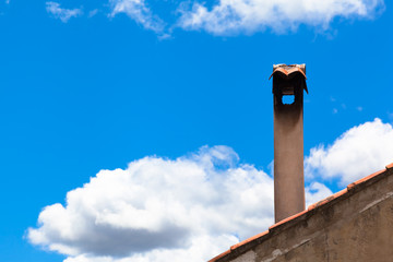Vintage Smokestack and Sky / Detail of old roof with shingles and nostalgic chimney in front of blue sky background, white clouds (copy space)