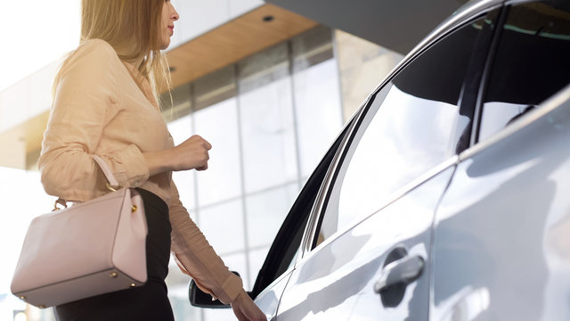 Successful female realtor getting into vehicle after working day in agency