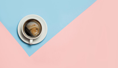 Flat lay of minimalistic picture of coffee on pink and yellow background.