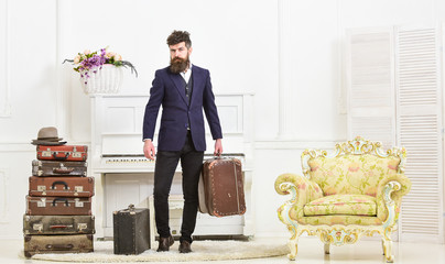 Macho attractive, elegant on strict face carries vintage suitcases. Man with beard and mustache wearing classic suit delivers luggage, luxury white interior background. Butler and service concept.