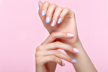 Poster de jardin Manicure Beautiful pink and blue manicure with crystals on female hand. Close-up. Picture taken in the studio