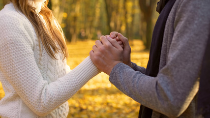 Guy warming his girlfriends hands, romantic atmosphere, date in autumn woods