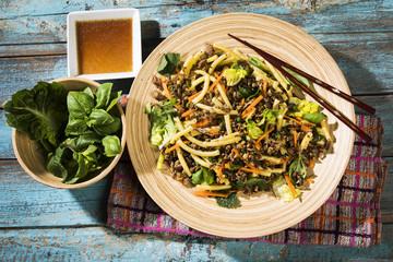 Asiatischer Hackfleischsalat mit Makkaroni, Ingwer, Chilis, Knoblauch, Karotten, Lauchzwiebeln, Soja-Zitronen-Dressing, Minze, Blattsalat und Basilikum