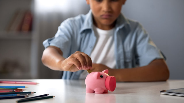 Little boy putting pocket money in piggy bank, raising funds for desired toy