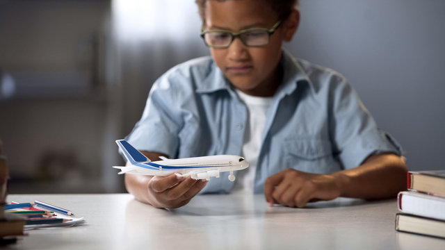 Boy dreaming of becoming pilot of modern airline and flying to faraway countries