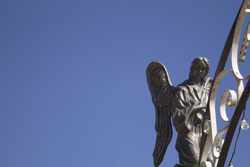 statue of an angel against the blue sky