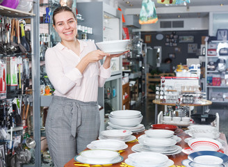 Female buyer choosing clay plates in the tableware store