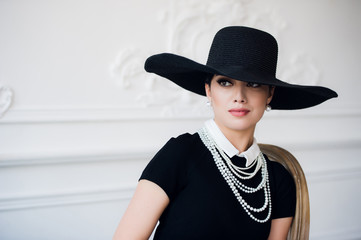 Portrait of a beautiful young woman in retro style in an elegant black hat and dress over luxury rococco wall background