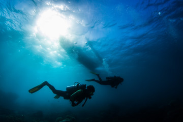 Wall Mural - Two divers swim underwater in a tropical sea with a silhouette of a boat over them. Philippines