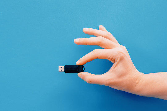 One hand holding pendrive on blue background