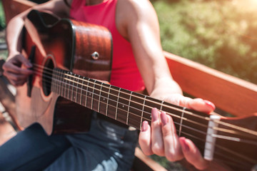 Close up of musician's hands playing the guitar. Girl is holding her fingers on guitar's strings. Girl is sitting on bench outside in this beautiful day.