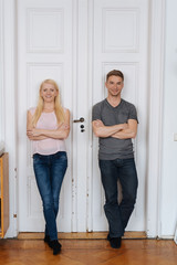 Trendy confident couple leaning against a door
