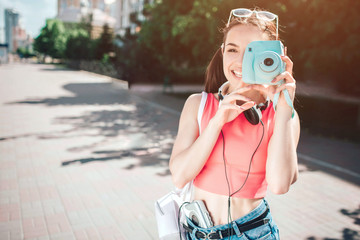 Nice melomanic girl is looking at camera though lenz of her camera. She is smiling. Girl has headphons around her neck and music player close to her body. She is happy.