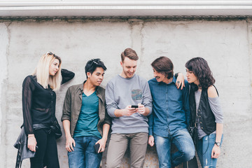 group of multiethnic friends millennials outdoor using smart phone having fun - youth culture, wifi technology, social network concept