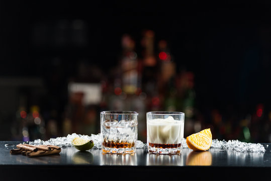 Two glasses of alcoholic drinks with ice on the table. With slices of lime and orange.