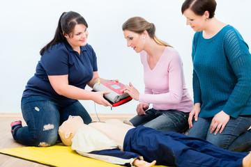 Erste-Hilfe-Kurs beim Üben mit Defibrillator
