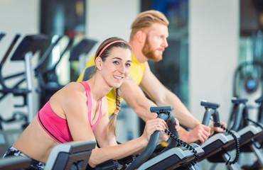 Fitness Frau und Mann beim Fahrrad fahren im Fitnessstudio