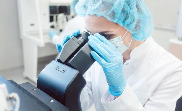 Wissenschaftlerin arbeitet im Labor am Mikroskop