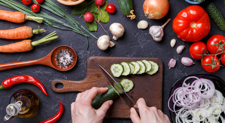 Picture on top of fresh vegetables, mushrooms, cutting board, oil, knife, hands of cook