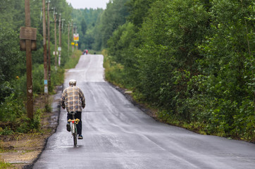 A man on a bicycle is driving on a road in the countryside