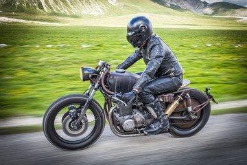 Biker with black leather suit and mask riding on a custom special rat motorbike. Speed and freedom concept