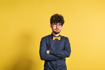 Portrait of a young man in a studio on a yellow background.