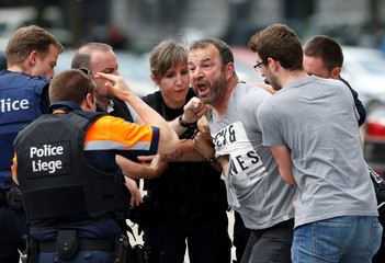 A man is taken away by police officers after crossing the security zone on the scene of a shooting in Liege