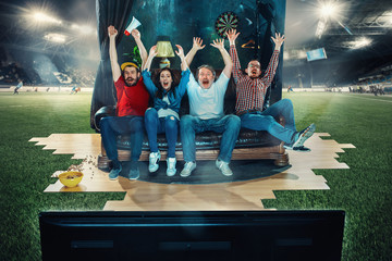 Soccer football fans sitting on the sofa and watching TV in the middle of a football field.