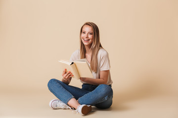 Photo of cheerful smiling woman wearing casual clothing sitting on floor with legs crossed and reading funny book, isolated over beige background