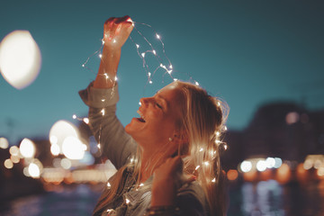 Happy young blonde woman garland fairy lights