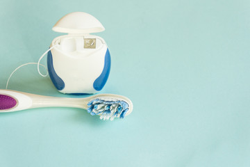 Toothbrush and dental floss on pastel color background. Copy space.
