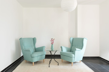 Detail of two turquoise armchairs in empty apartment